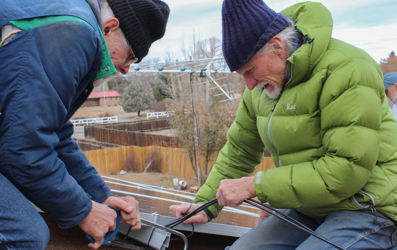 John Lyle, right, helps Chuck Haspels install solar panels on his roof. Lyle is the leader of Solar Barn Raising, a group of volunteers installing solar energy systems for free in southwest Colorado.