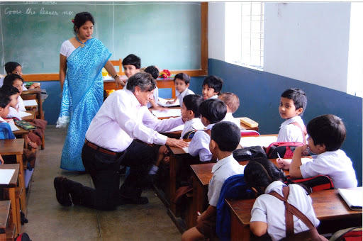 Dr. Rabindra Roy, kneeling, speaks with schoolchildren in an Indian school he envisioned and funded with his wife. (Photo