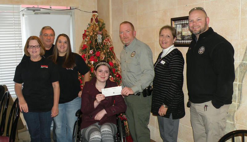 Sophia Greenwalt With a Helping Hats Presentation to the Stone County Shop With a Cop Program