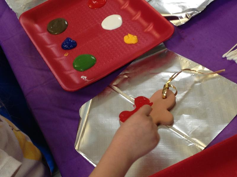 Painting a ceramic gingerbread figure ornament.
