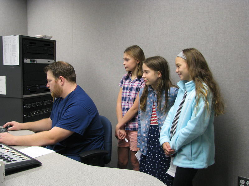 Students (Left to Right: Kaili Keeth, Annie Beatty, and Quincy Alberhasky) of Mrs. Hopkins and Mrs. Wheeler's classrooms watch as their segment is made ready for radio.