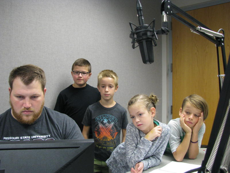 Students (From Left to Right: Ethan Pitts, Ralph Johnson, Goldie Winstead, and Misha Trimble) watch as KSMU Production Assistant Peter Batemon edits their segment for brodcast.
