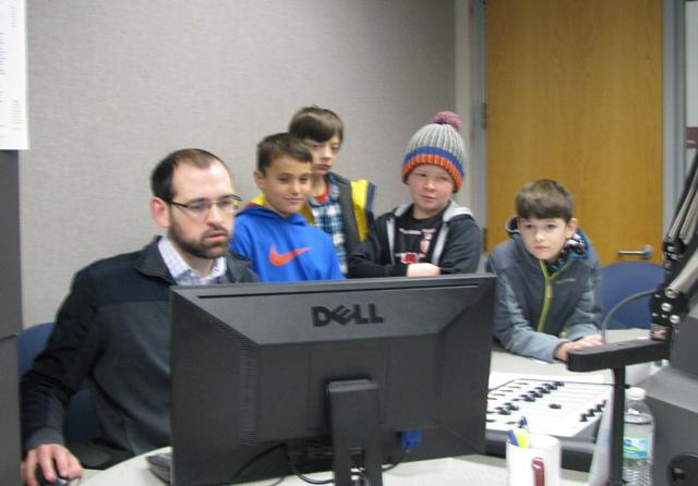 Rountree Elementary students (Left to right: Ryan Doel, Finlay Maloney-Tubbs, Jackson Brownfield and Eli Moody) help edit their episode of the Rountree News Update with KSMU's Scott Harvey.