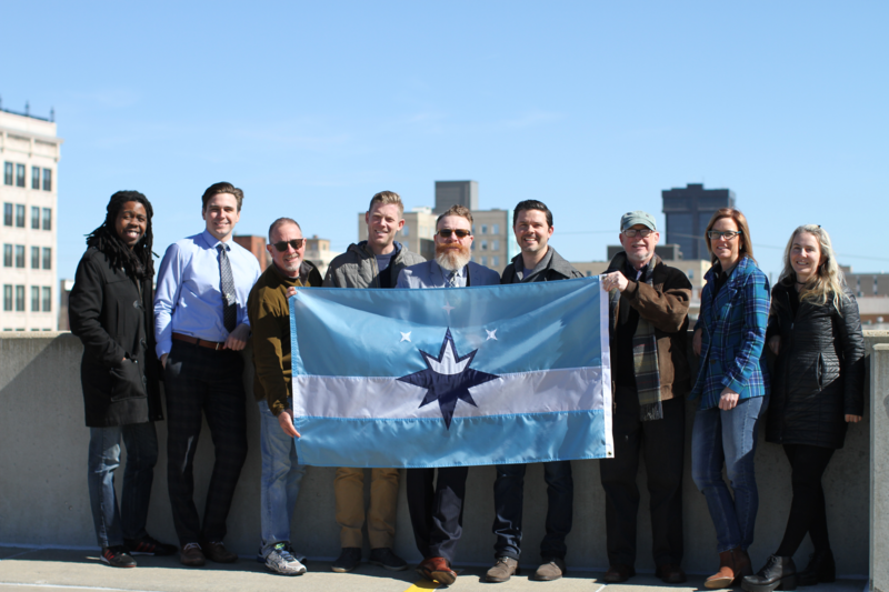 John McQueary (Center-right) poses with the new flag created by the Springfield Identity Project