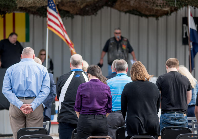 President of American Legion Post 639, Terry Willey, leads audience members in a moment of silence for POWs and MIAs during the unveiling of Special Agent Joseph M. Peters Hero's Way Highway sign.
