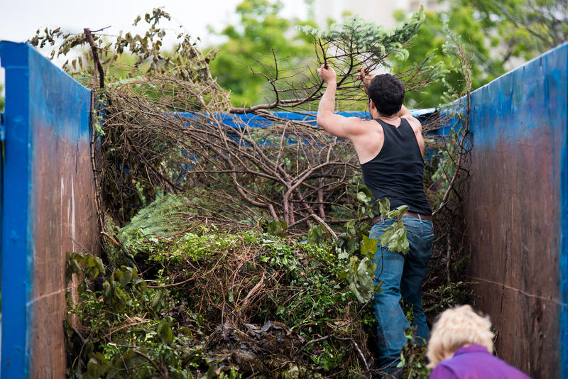 Phil Caudle, who lives in Phelps Grove, throws branches that were dropped off into a dumpster. Phelps Neighborhood Association held a neighbor cleanup day for Phelps Grove 8 a.m. to 12 p.m. on May 20, 2017.