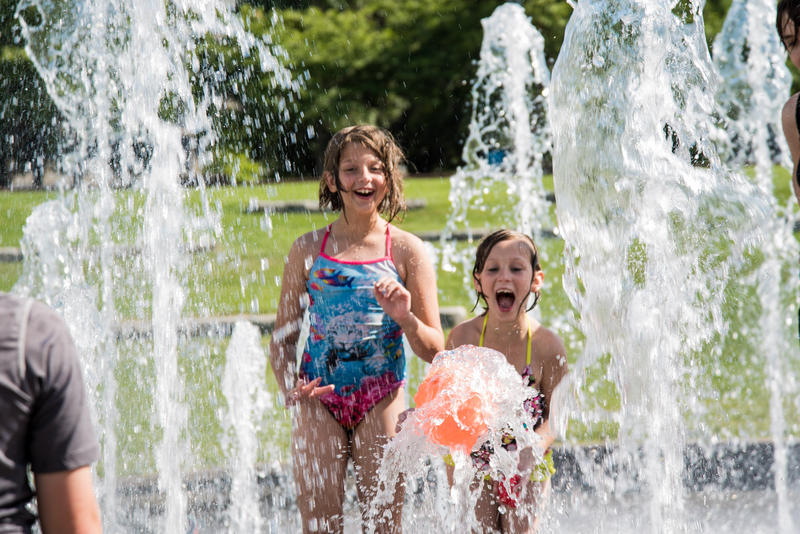 Madison, 10 (left) and Mia, 8 (right) Kleier get excited as they finally get the ball to stay in the stream of water that is part of the Jordan Valley Fountain. Temperatures reached 95 degrees in Springfield causing many to seek cooler activities.
