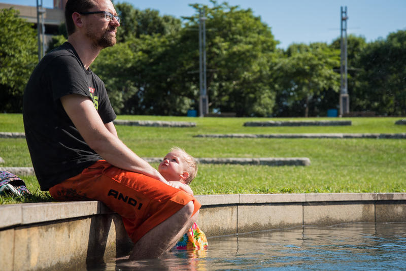 As he watches two of his daughters play in the Jordan Valley Fountain, Kevin Kleier's youngest daughter, Brooklyn, watches her dad. Temperatures reached 95 degrees Wednesday July 12 in Springfield.