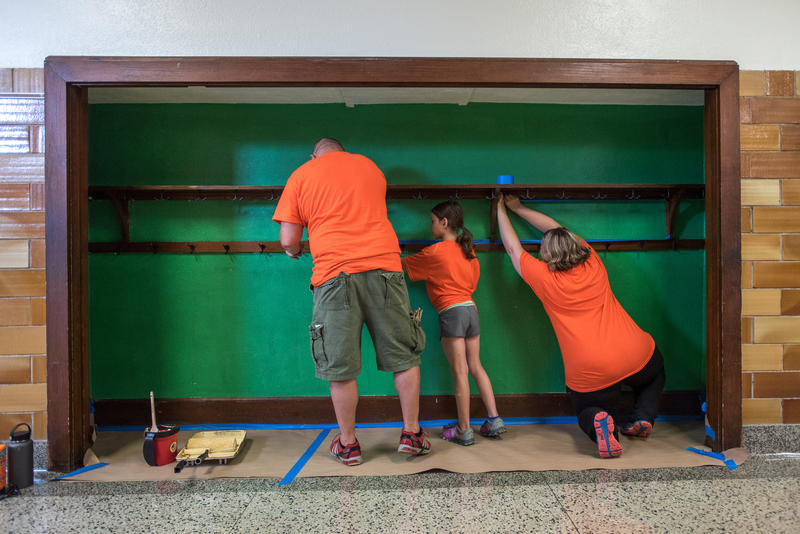 Ty Heinrichs, left, along with daughter Riley, 8, and wife Christy, paint a hallway nook in Bowerman Elementary as part of Habitat for Humanity's ongoing Neighborhood Revitalization program for Woodland Heights.