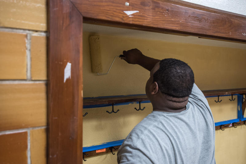 Lawrence LeFlore, who is with Courageous Church, paints a hallway nook in Bowerman Elementary as part of Habitat for Humanity's ongoing Neighborhood Revitalization program for Woodland Heights.