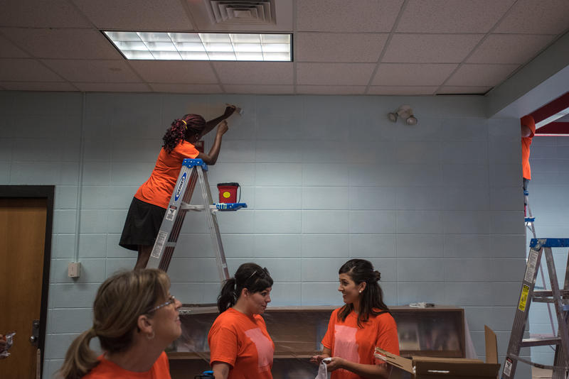 Natasha Brown, who is with Courageous Church, paints a section of a wall in the Bowerman Elementary's library as part of Habitat for Humanity's ongoing Neighborhood Revitalization program for Woodland Heights.