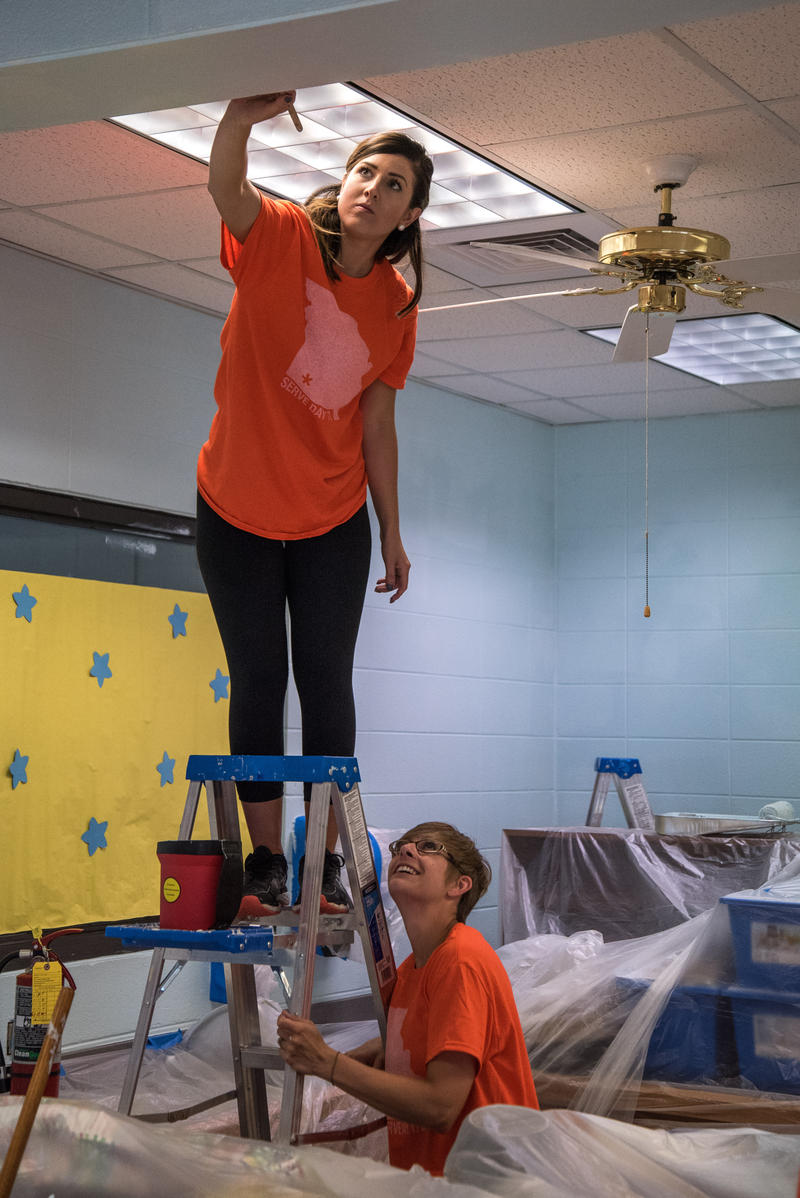 Kelly Hunt paints a section of a wall in the Bowerman Elementary's library as Whitney Evans holds the ladder. Both women are with Courageous Church which is working with Habitat for Humanity's ongoing Neighborhood Revitalization for Woodland Heights.