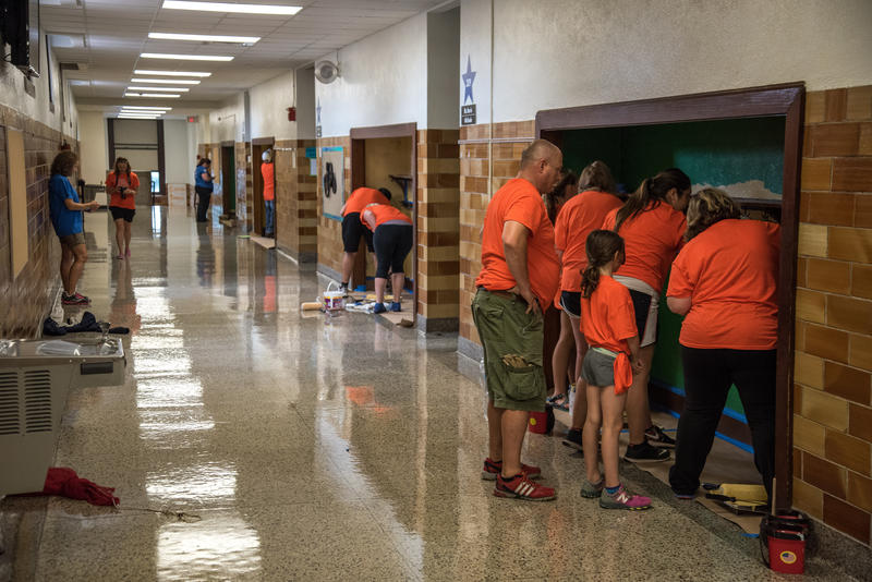 On the second floor of Bowerman Elementary School volunteer's work on painting hallway nooks as part of Habitat for Humanity's ongoing Neighborhood Revitalization program for Woodland Heights.