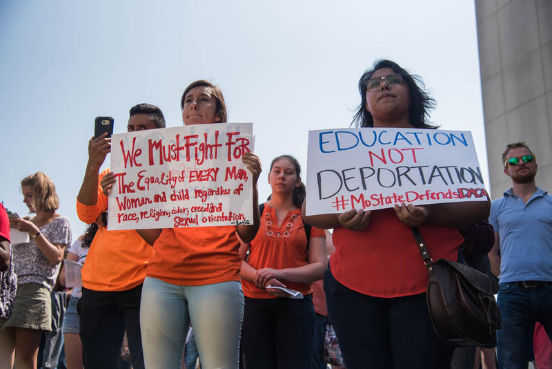 Students in orange stand in front of Strong holding signs of support for DACA students.