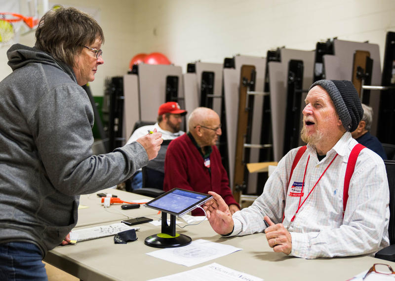 Kathy Eubanks (left), 65, is verified by election official Kenny Knauer (right), 74, at Roundtree Elementary School on Nov. 7.