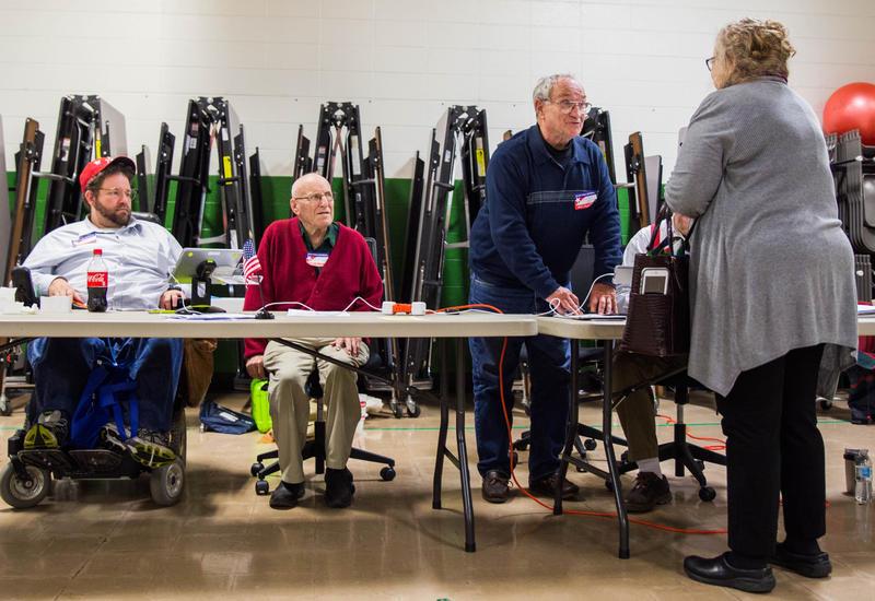 Election officials Brett Kelly (left), 35, Erwin Busiek (center), 89, and Nolan McCaulley (right) assisted voters like Dr. Teresa Olsen (far right), 65, at Roundtree Elementart School on Nov. 7.