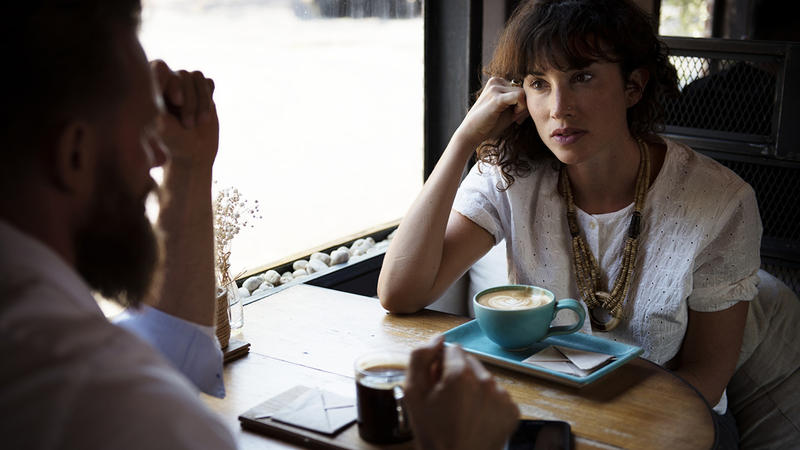 A man and a woman having a conversation at a cafe.