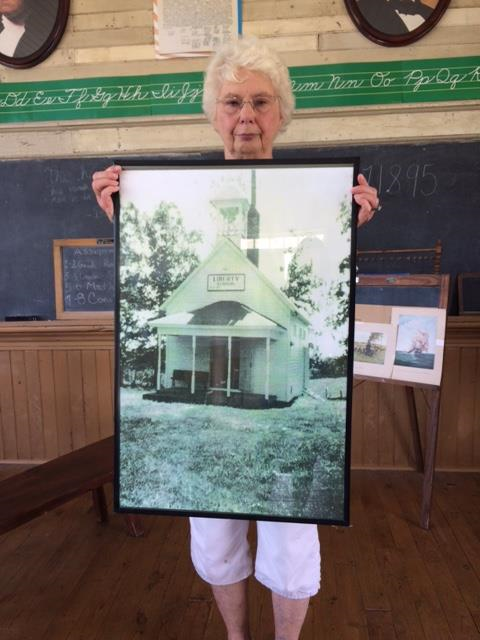 Norma Tolbert holding a picture of Liberty School in its original location