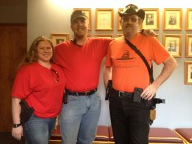 Gun owners Sherry Lloyd, Christopher Lloyd and Bruce Cook (l to r) display their firearms at the Ashland City Council hearing on a proposed gun control ordinance