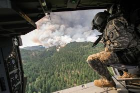 An Oregon Army National Guardsman looks for spot fires around the Government Flats Complex fire from a Blackhawk helicopter, near The Dalles, Aug. 21, 2013.