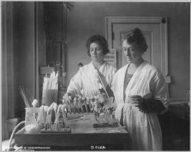 Medical workers test a serum in a lab, a century ago.