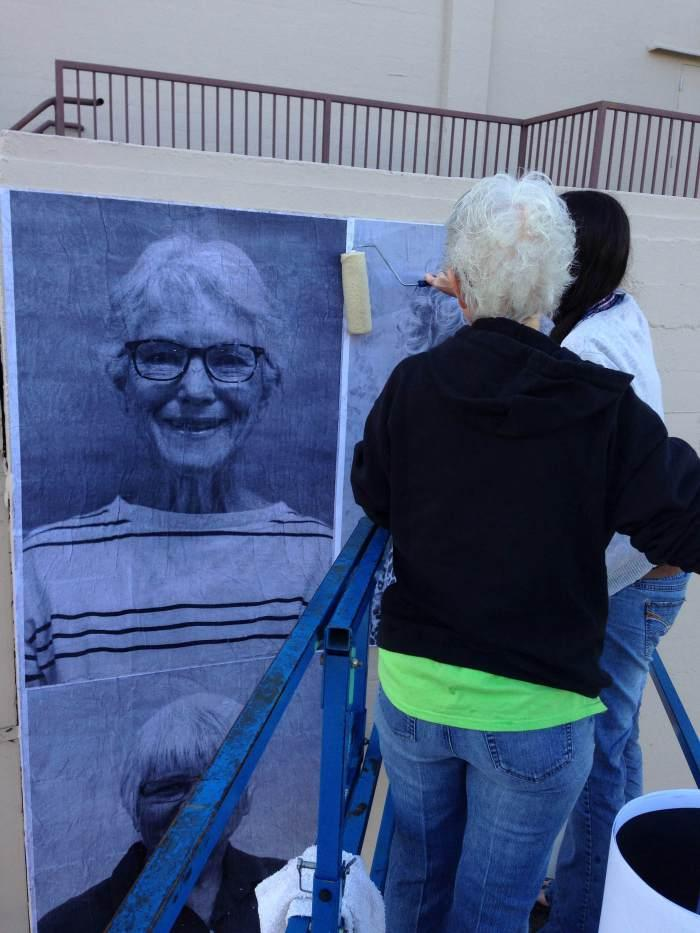 Redding City Councilor Francie Sullivan helps Misty McCraney paste Sullivan's portrait on one a downtown wall.