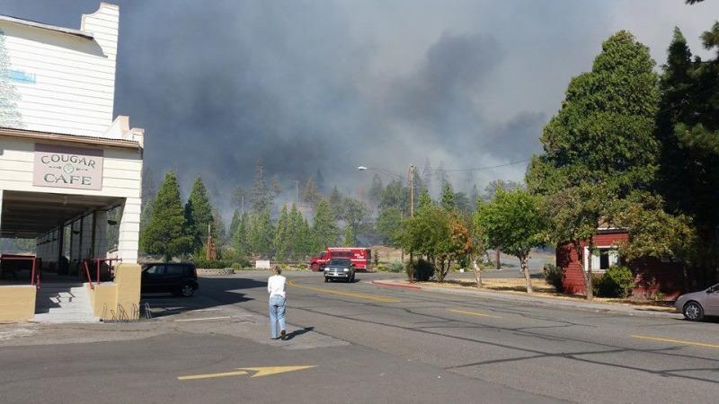 A woman watches the Boles Fire burn near the high school