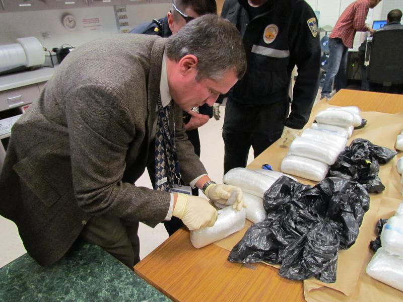 Lieutenant Kevin Walruff, commander of MADGE, inspects seized drugs.