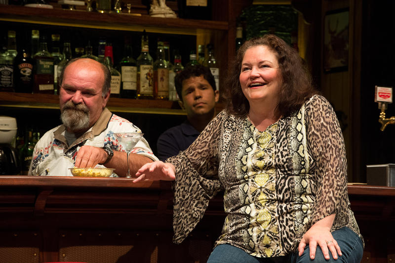 Jessie (K.T. Vogt) recalls her plan to see the world at her 45th birthday celebration with bartender Stan (Jack Willis) and Oscar (Carlo Albán).