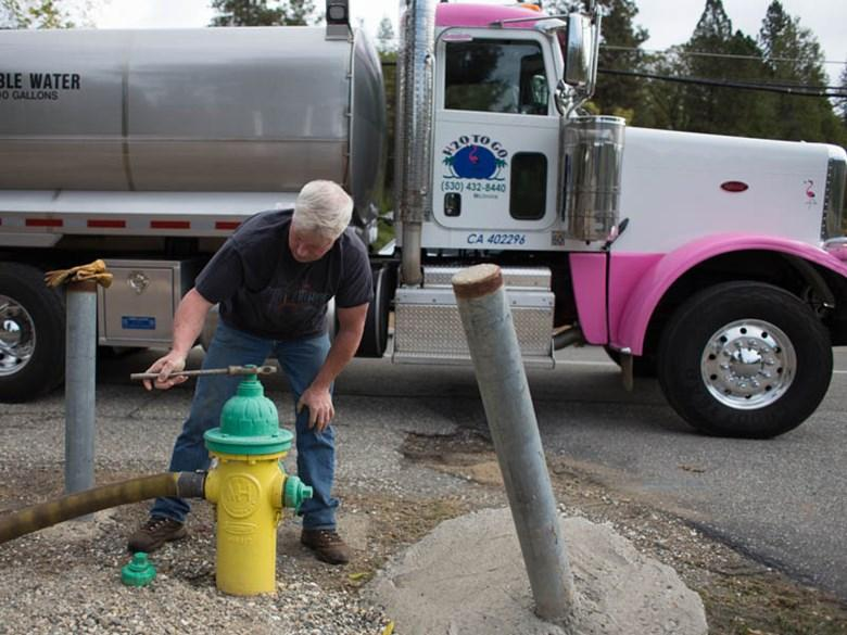 """Garrett McInnis with """"H2O to Go"""" water hauling taps hydrant to fill his tanker truck."""
