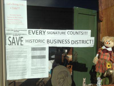 Signs in the window of a downtown Fort Bragg business urge residents to sign a petition for a ballot measure that would prohibit social service agencies in the downtown area.
