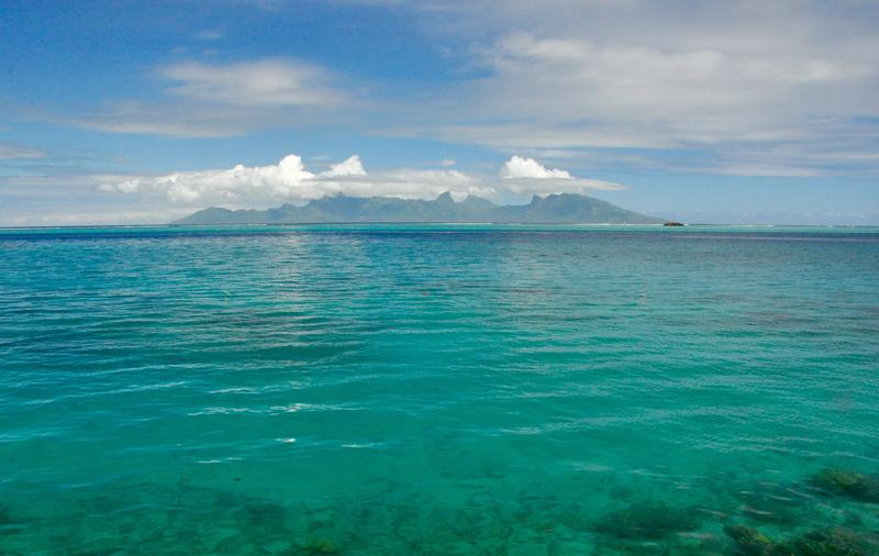 Off the coast of Tahiti, the island of Moorea rises like a vision across emerald waters.