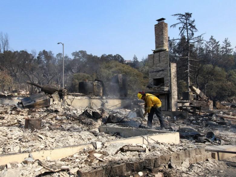 "Berkeley firefighter Matt George picks through the ash of a Santa Rosa neighborhood looking for smoldering materials Oct. 12, 2017. ""It's unbelievable, the destruction,"" he says."