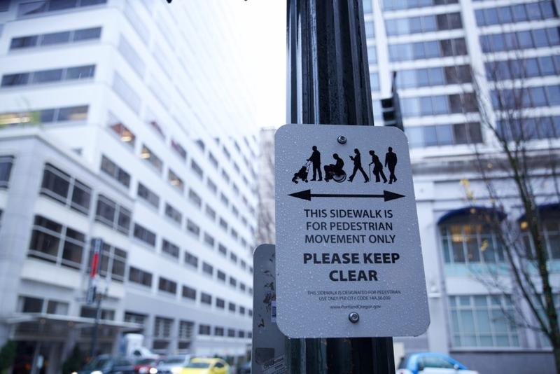 Signs prohibit people from blocking pedestrian traffic in front of the Columbia Sportswear Flagship Store in Downtown Portland.