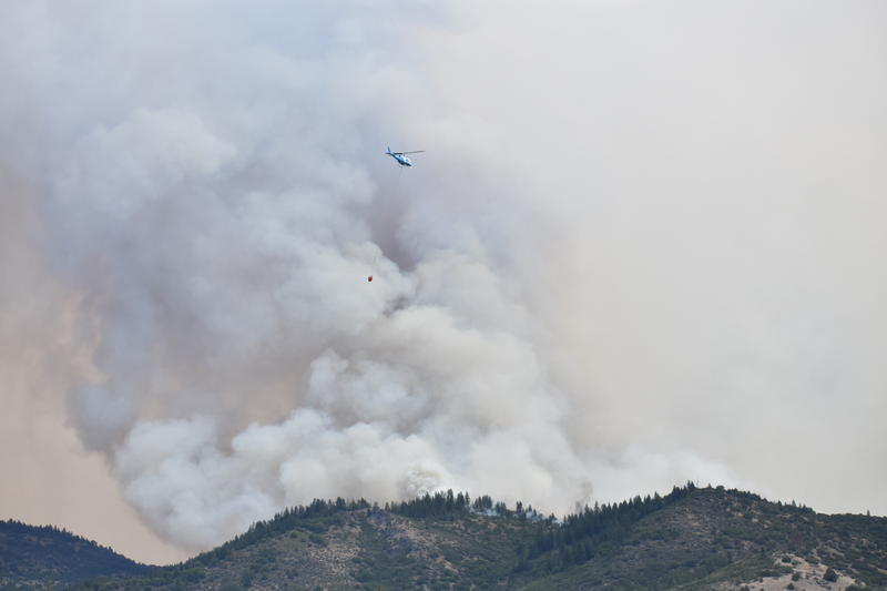 A helicopter prepares to make a drop on the Klamathon fire. Officials say there are 21 helicopters working the fire. As of Monday evening, they had dropped 575,000 gallons of chemical retardant and 942,000 gallons of water.