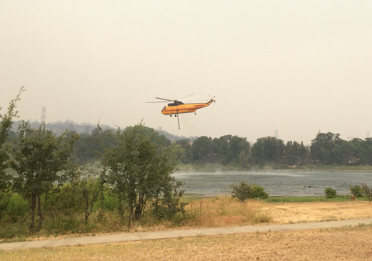 A helicopter dips into Mary Lake for water before heading toward active flames at the Carr Fire.