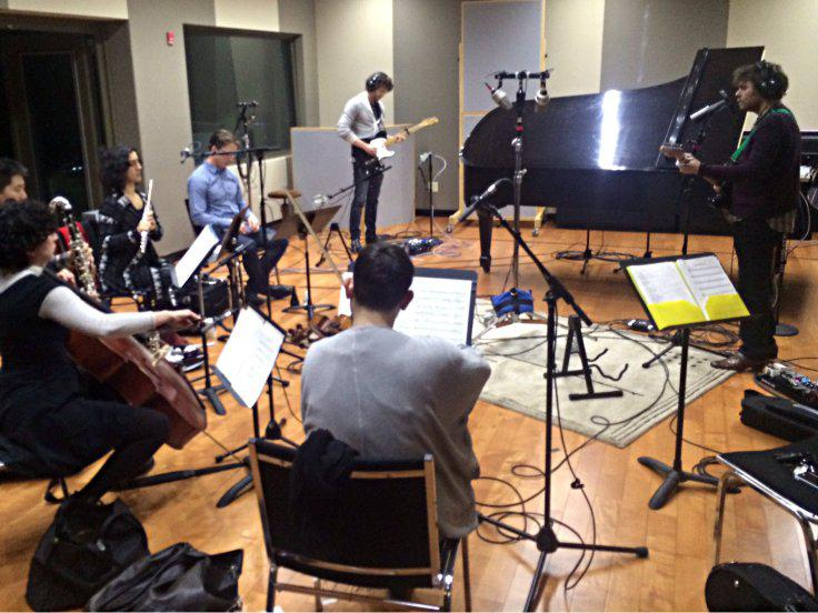 Gabriel Kahane, on the right with the guitar, composed a new work on homelessness for the Britt Orchestra for a July 27th concert.