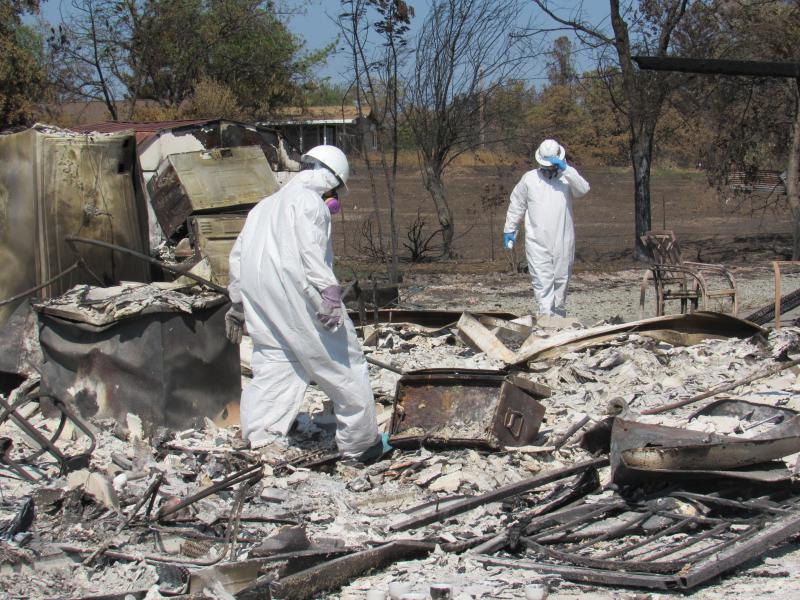 Haz-mat workers sift through the ashes and rubble of a burned home in Redding. They're looking to identify and remove hazardous waste items as Phase One of the post-fire cleanup process.
