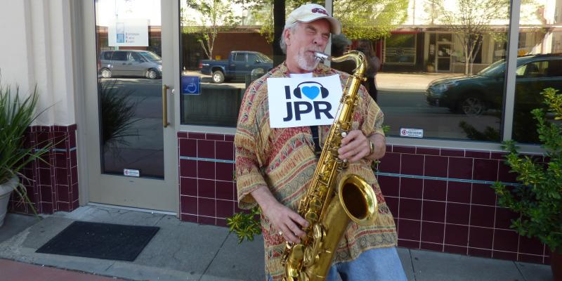 JPR Late Night Blues Volunteer Host Derral Campbell toots his horn for JPR in front of the JPR Redding studio.