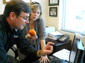 Larry Thompson shows TPR's Eileen Pace how to find clues that a website is safe.