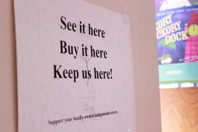 This sign encourages people who are browsing and buying online to help support the local store instead.