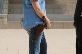 One of the moms with the group Moms With Guns Demand Action wears her firearm at the press event.