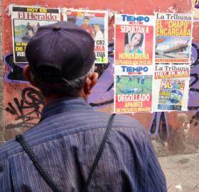 A passerby reads the day's bloody headlines in Tegucigalpa, the capital of Honduras.