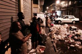 Street people of Tegucigalpa pick through the day's garbage in the rain, looking for salvage they can sell.