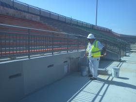 Joe Aguilar, who says he has worked only about a month for the painting contractor for the Alamo Stadium project, paints the walls of the stadium days before the facility's grand re-opening.