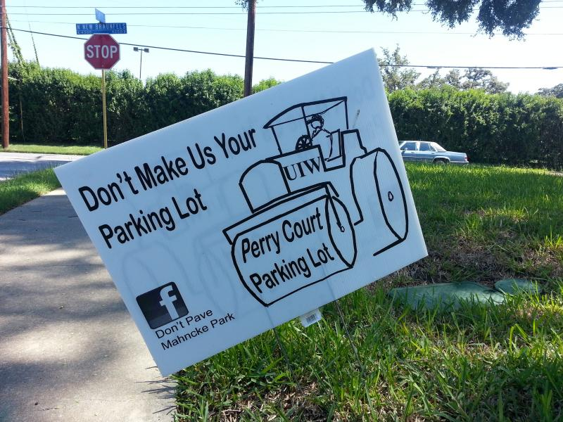 Some residents along Perry Court display signs in their yards opposing the parking lot on their street.