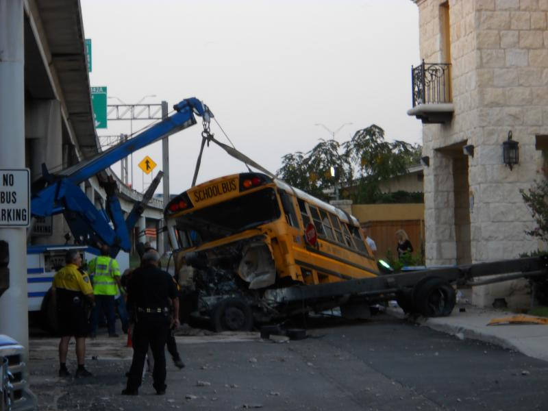 An SAISD special needs bus is inspected by SAFD and district officials. The three people inside – the driver, an assistant, and a student – were all taken to University Hospital to treat non-life threatening injuries.