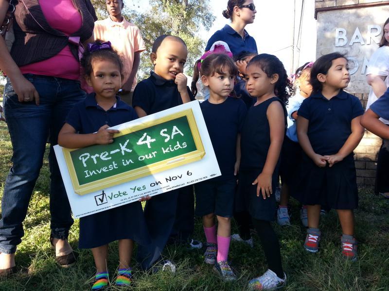 Children hold signs for the mayor's Pre-K 4 SA measure outside the Barbara Jordan Community Center Oct. 24
