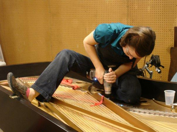 Emily Townsend repairing a piano.