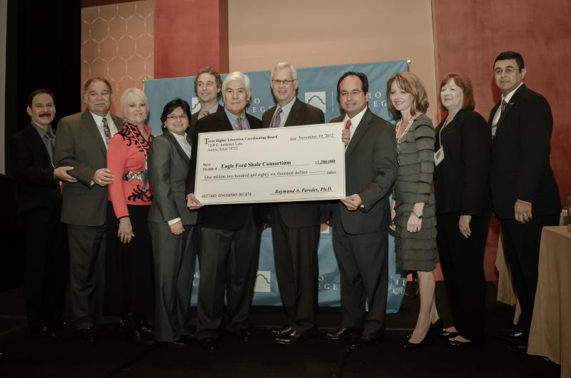 Texas Higher Education Coordinating Board Commissioner Raymund Paredes, left holding check, with members of the Eagle Ford Shale Consortium